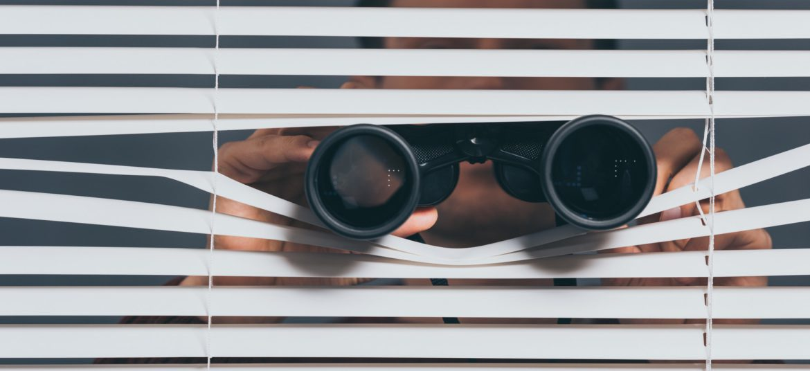 suspicious young man with binoculars spying through blinds
